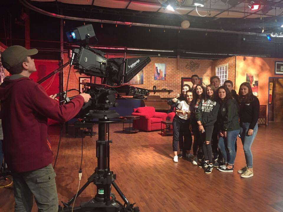 students pose in front of broadcast camera at w s k g