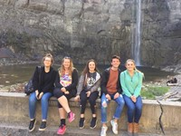 group of students sitting in front of water falls