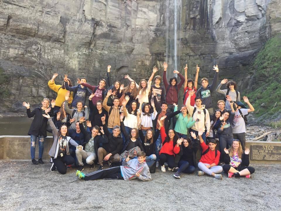 group of students wave at water falls