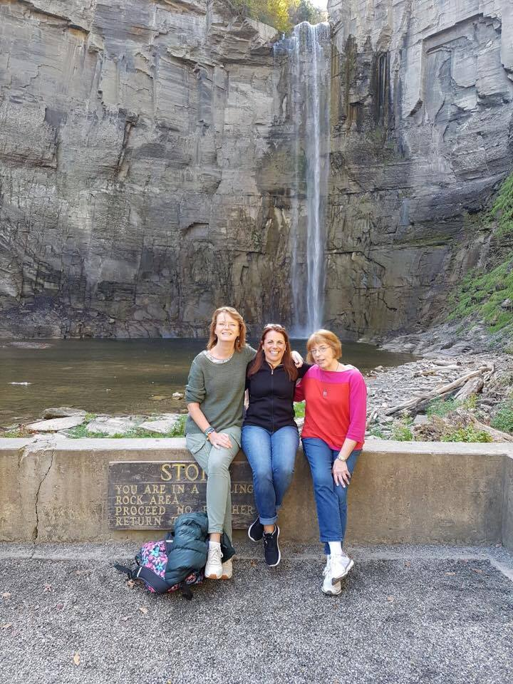 farther shot of teachers posing by water falls