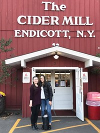 two female students smile in front of the cider mill