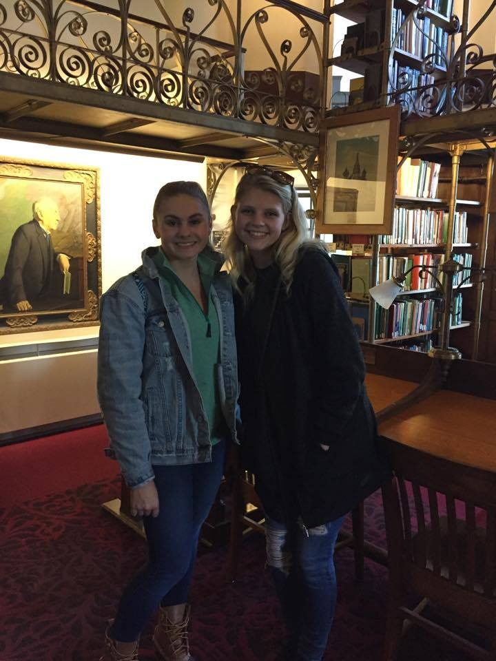 two female students pose in a library
