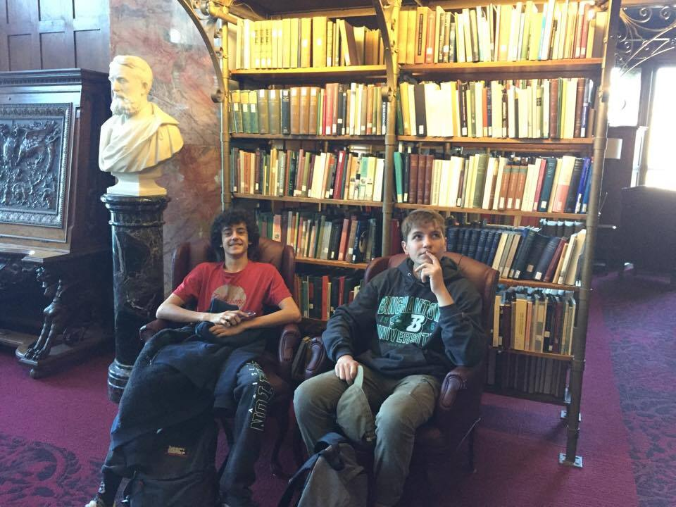 two male students pose in a library