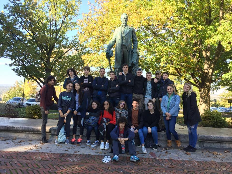 students pose with a statue