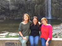 teachers pose for a picture in front of falls