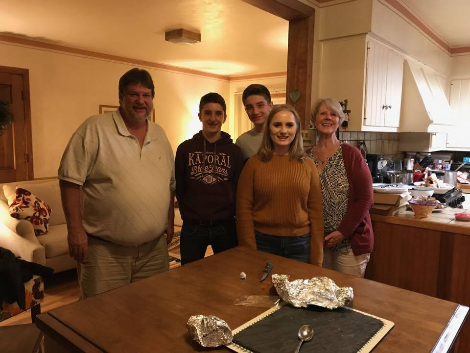student and family smile in kitchen