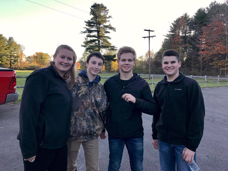 four students smile outside