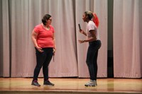 two female middle school students acting in play