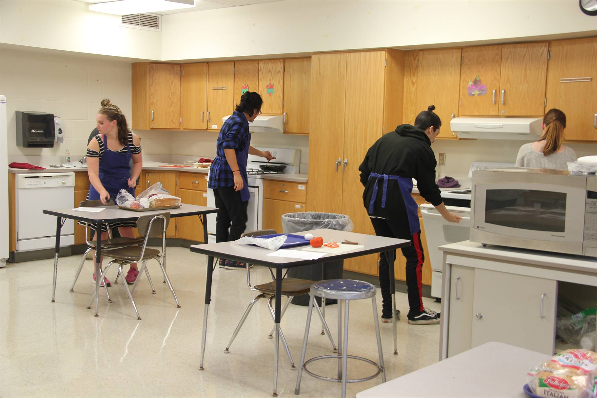far shot of students making grilled cheese in the kitchen