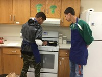 students work on grilling grilled cheese on stove top