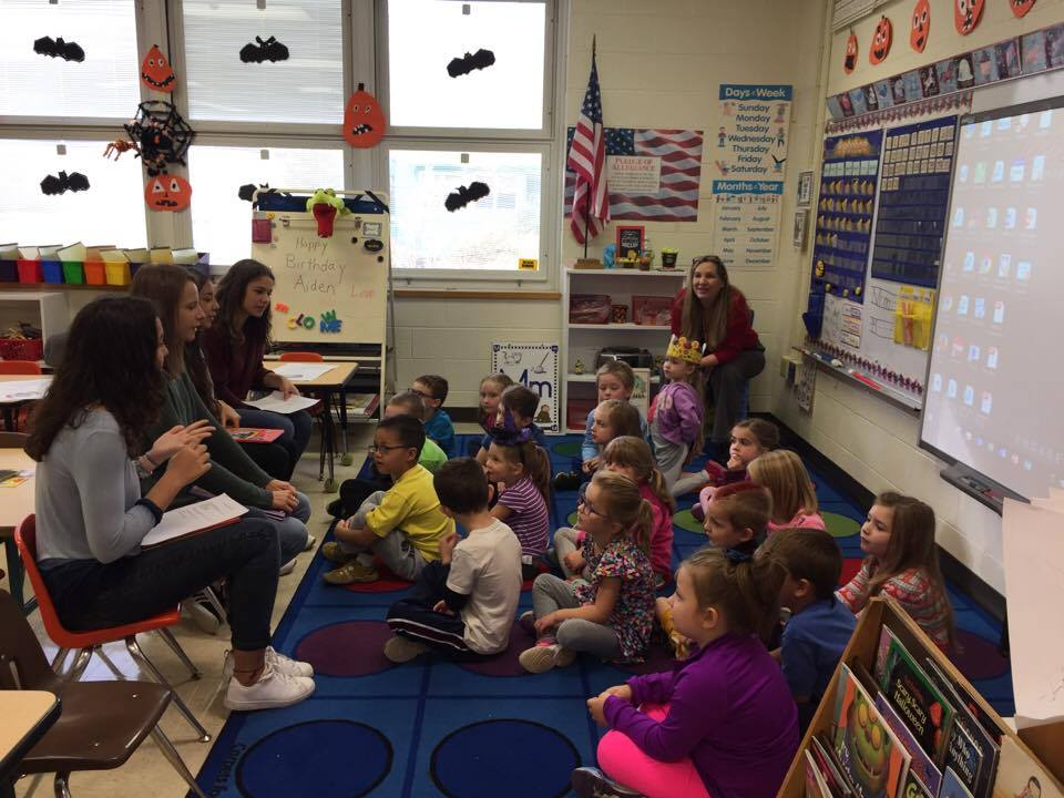 group of students talk to elementary students