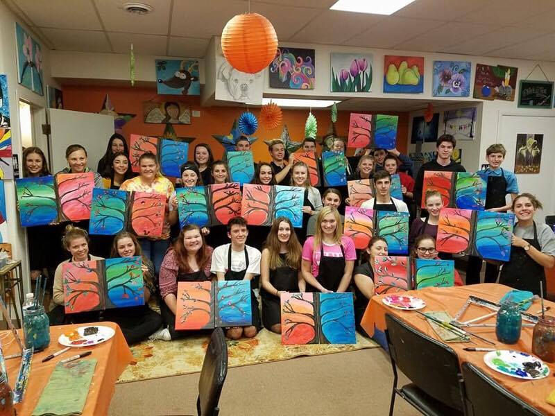 students hold up paintings of trees with their american counterparts