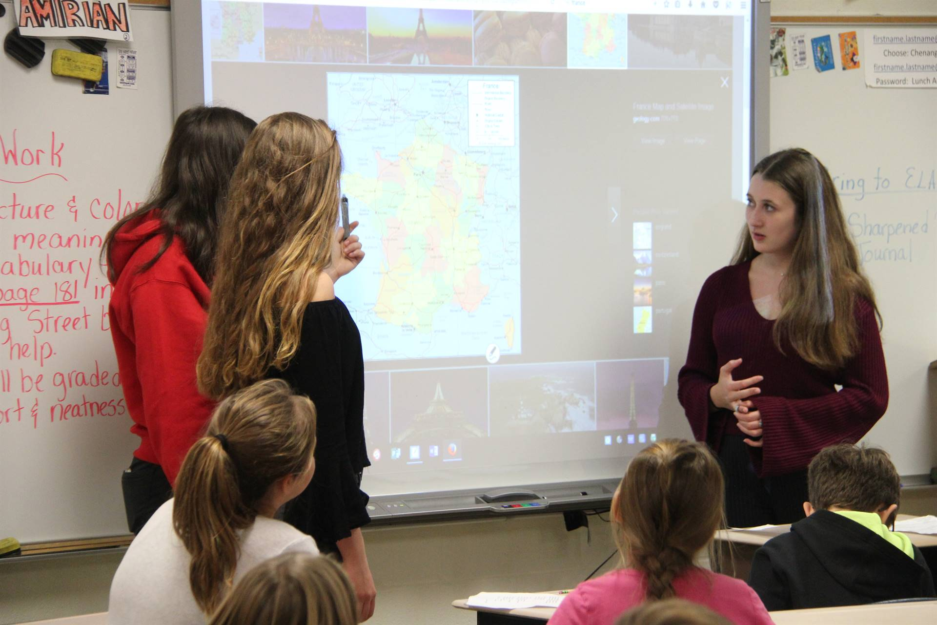 up close of students pointing to map of france on board