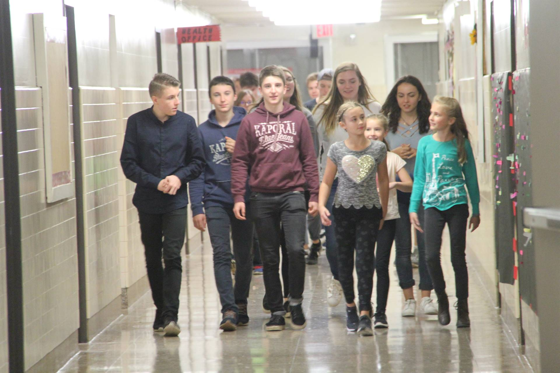 elementary students walking down hallway with french exchange students