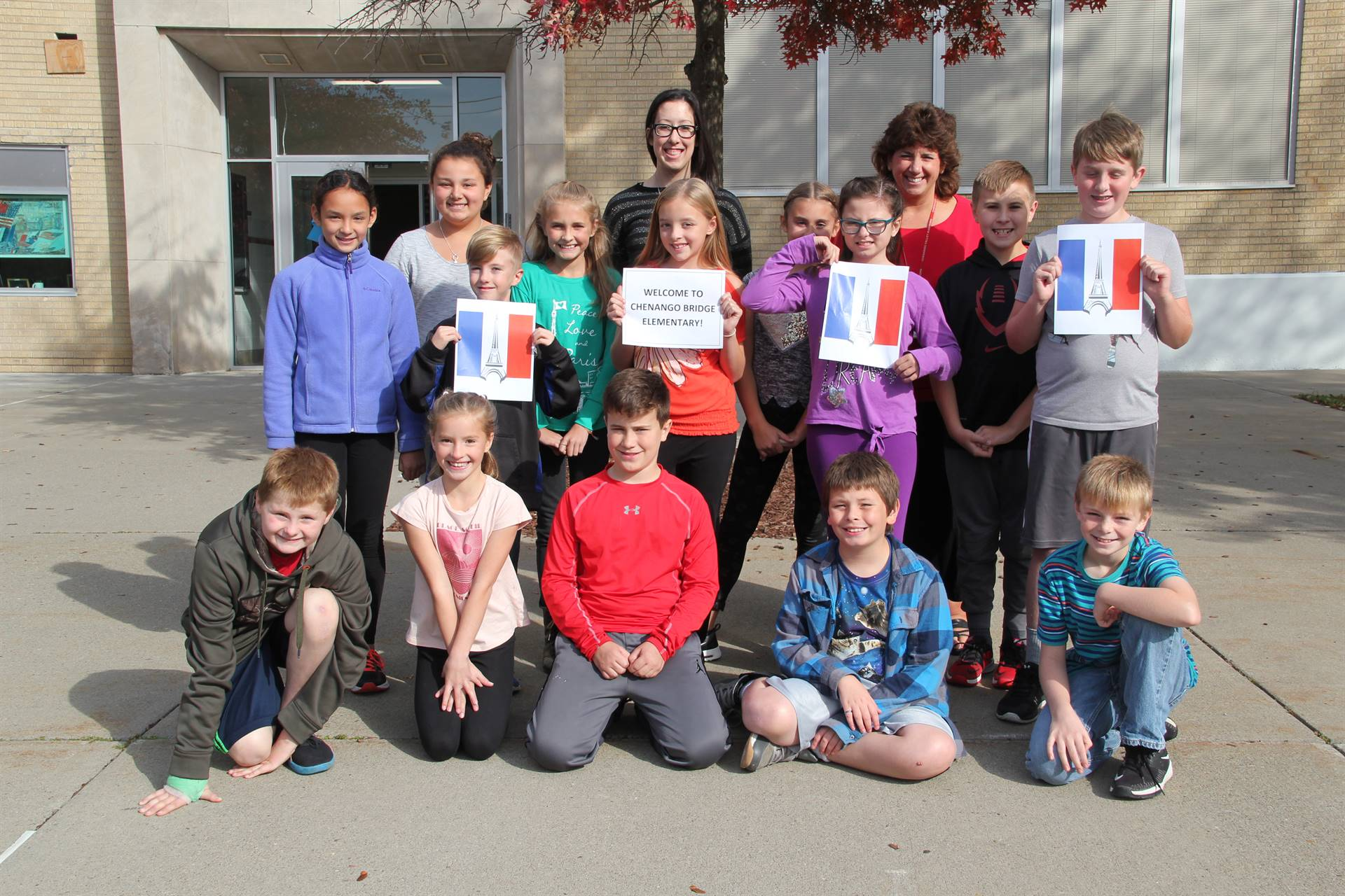 group of chenango bridge elementary student council members hold up signs to welcome french exchange