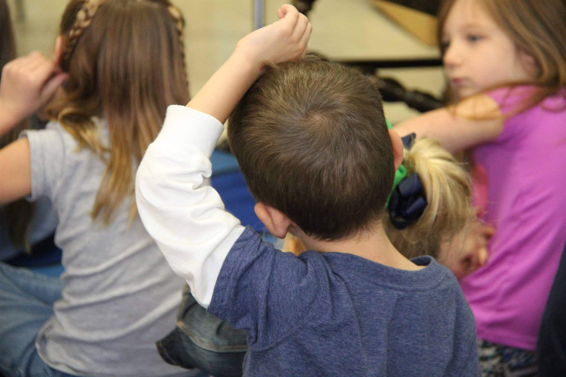 elementary student raising hand to ask a question