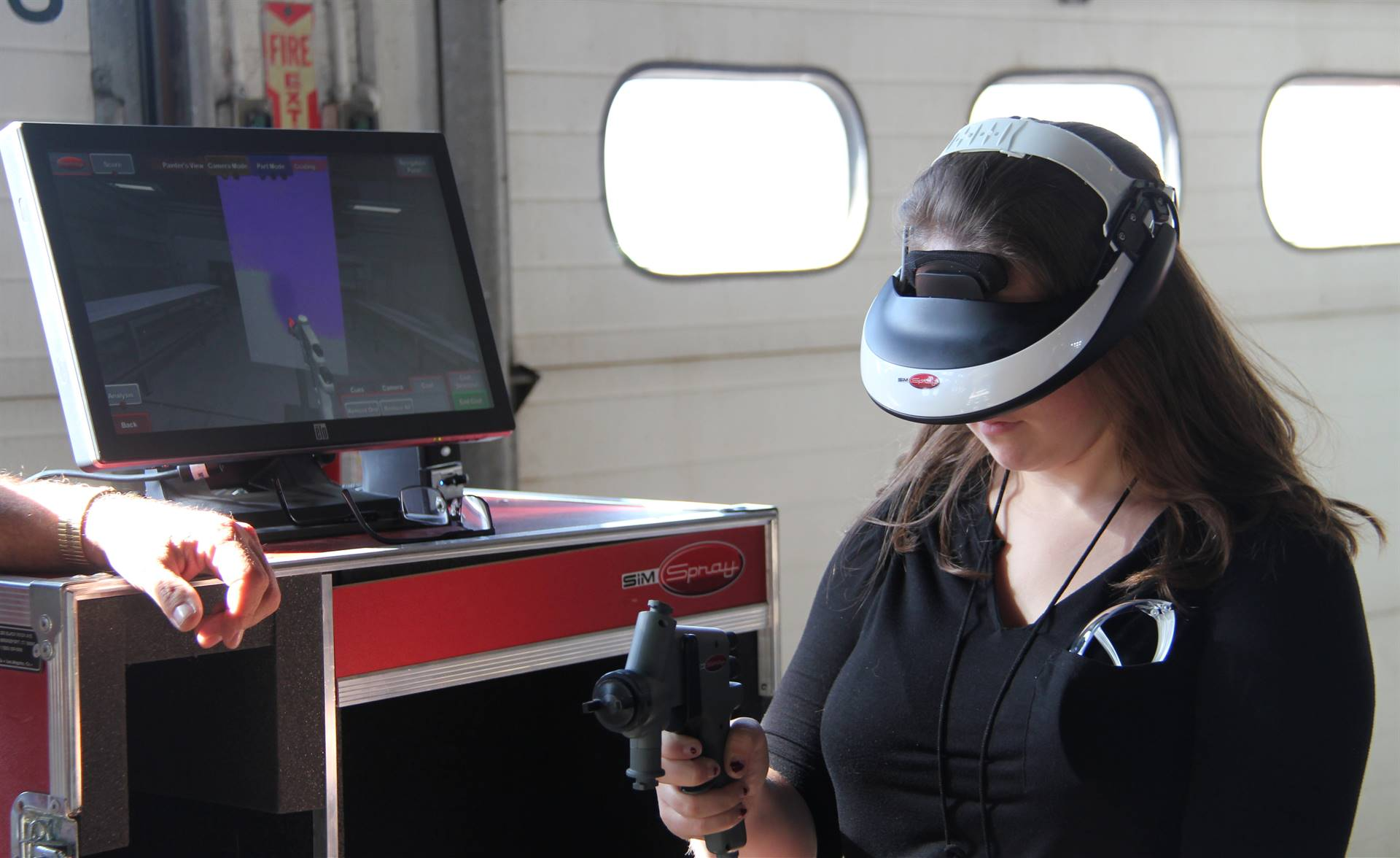 another student tests out virtual reality painting equipment at construction career day
