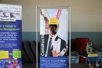 another student smiles inside of construction career day college poster