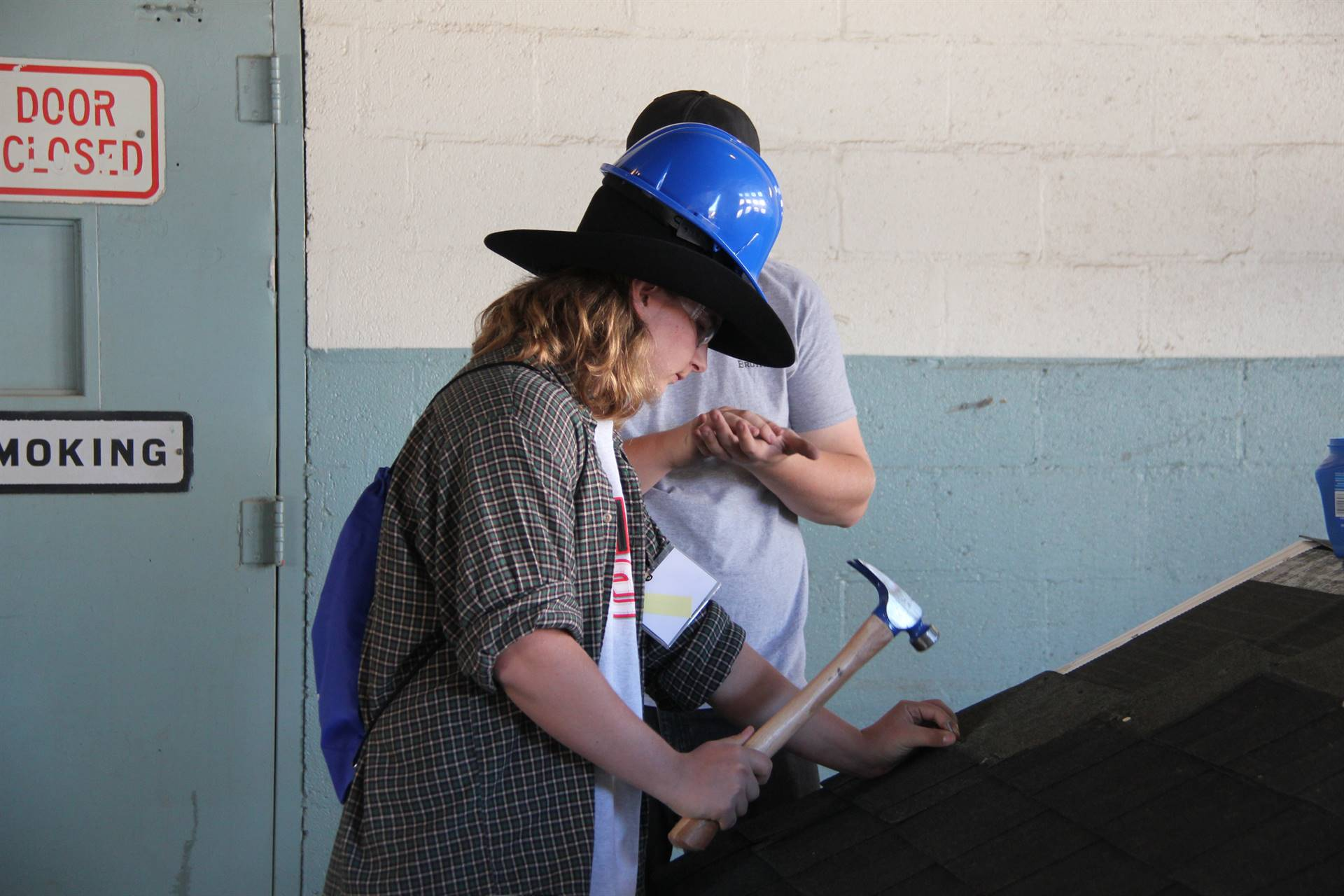 student tries out roofing on a sample roof with hammer and nail