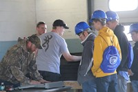 students talk with roofer inside at construction career day