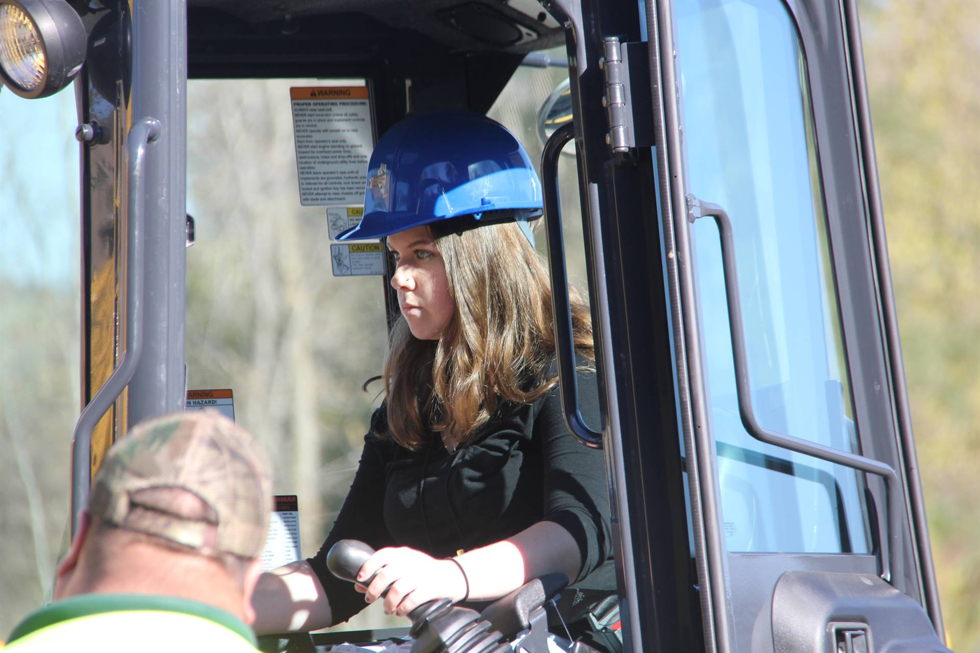 closer shot of student inside equipment picking up rocks on construction career day