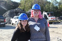 two female students smile in front of construction materials in the background
