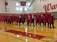 girls swim team does an enthusiatic dance during high school pep rally