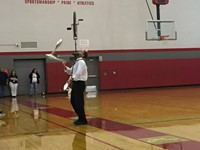 mister stafford juggling with a unicycle balancing on his face at pep rally