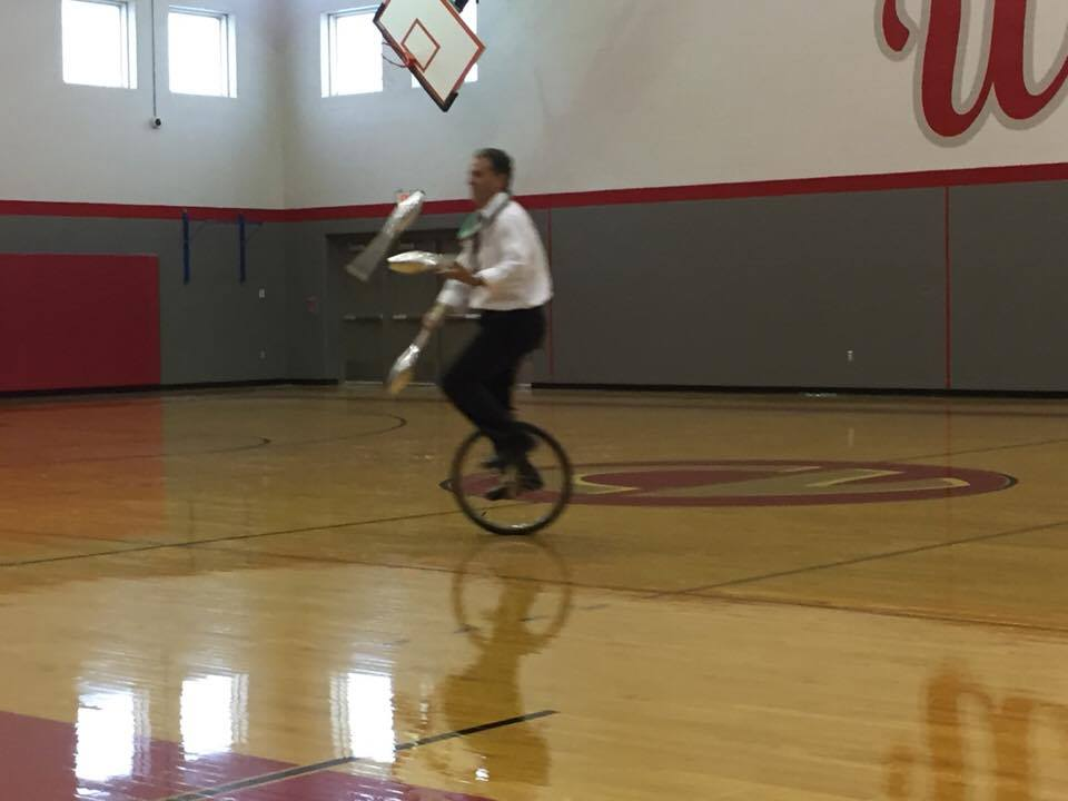 mister stafford juggling while riding a unicycle