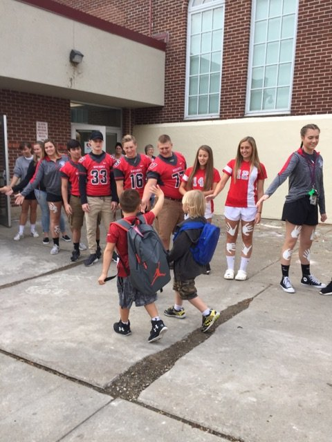 student athletes give students high fives as they enter port dickinson elementary