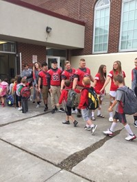 student athletes give port dickinson elementary students a high five as they enter the school buildi