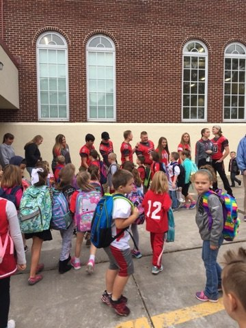 high school students give students at port dickinson elementary a warrior welcome greeting