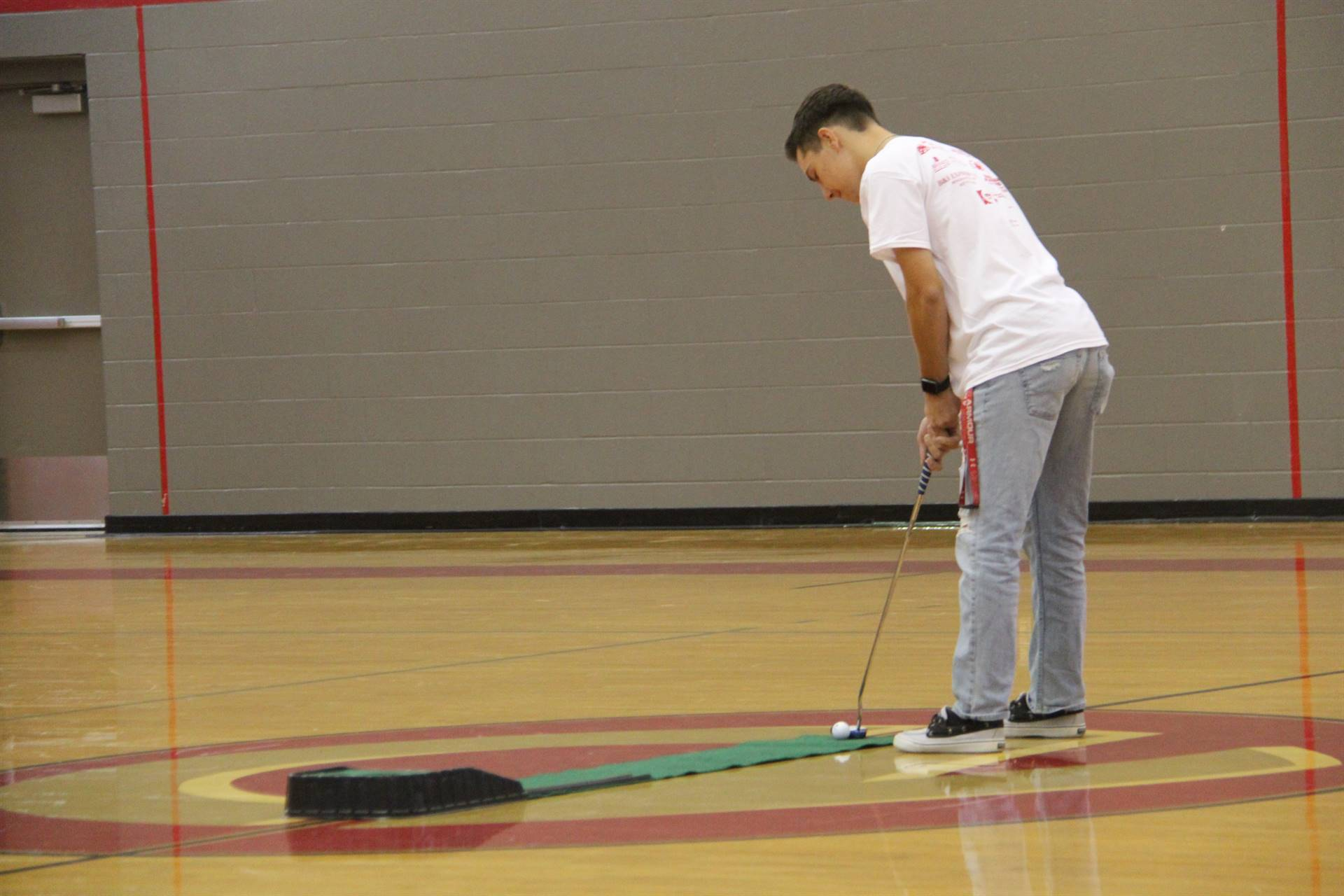 high school golf team member does a putting challenge during high school pep rally