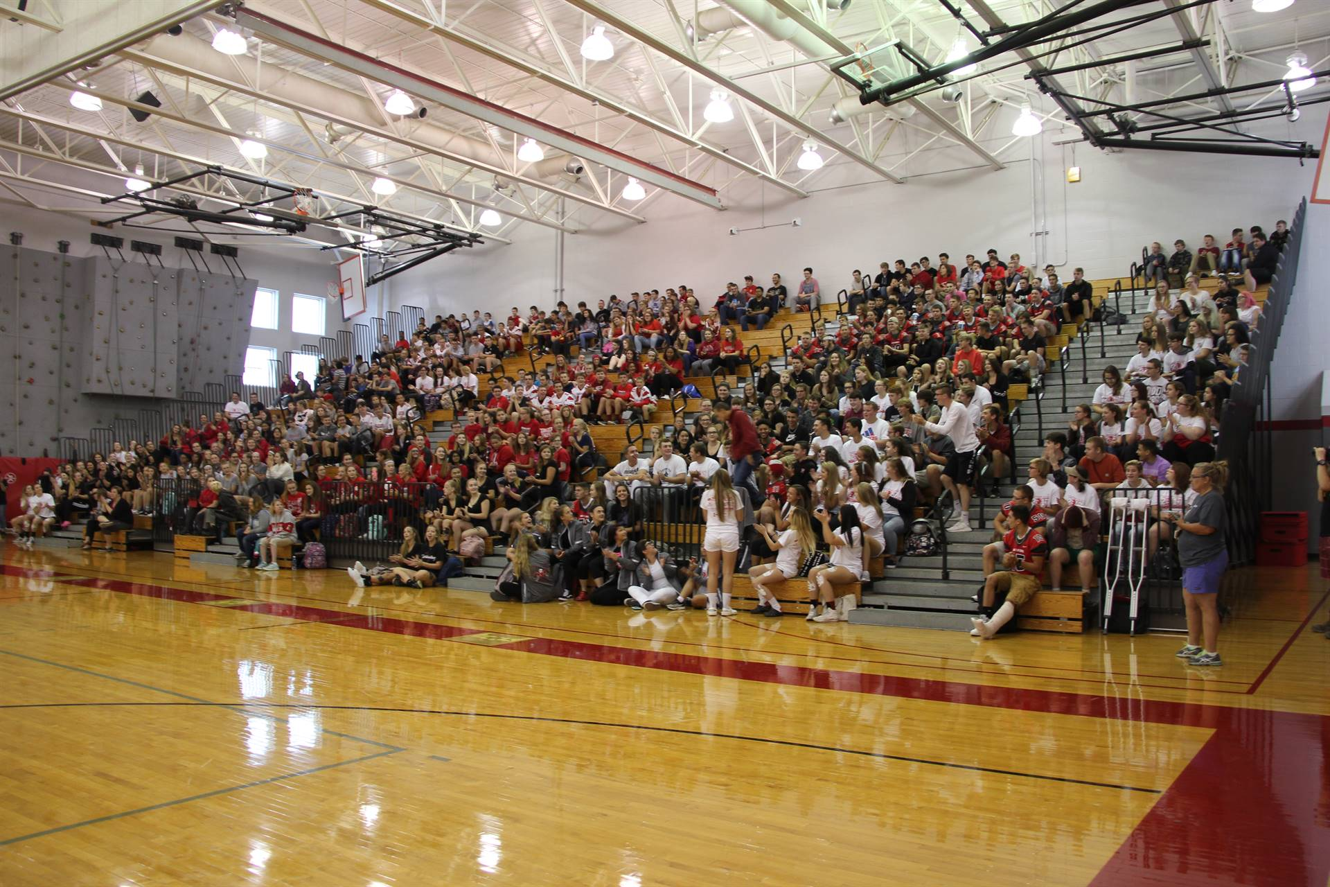 far shot of students in bleachers at high school pep rally