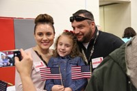 veteran parents smiling with daughter
