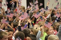 students sitting waving american flags in the air