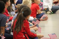 students holding small american flags