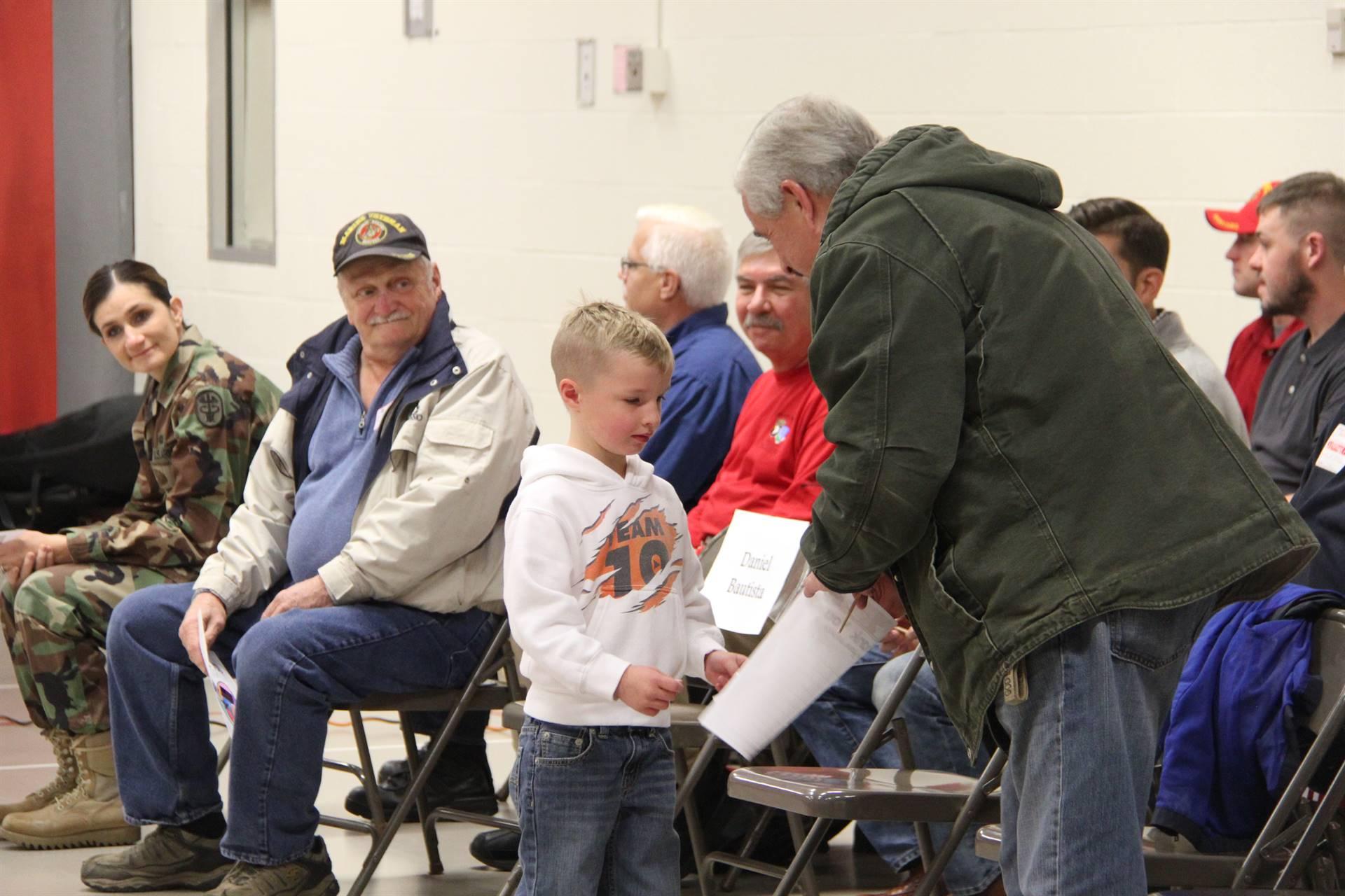 student handing veteran thank you card