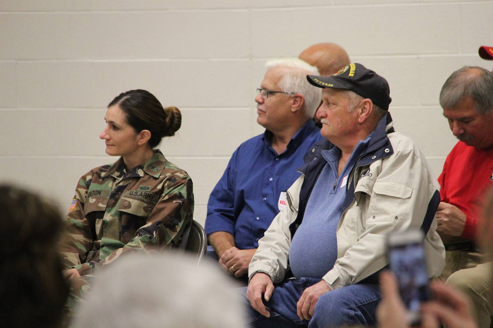 veterans listening to students read patriotic poems