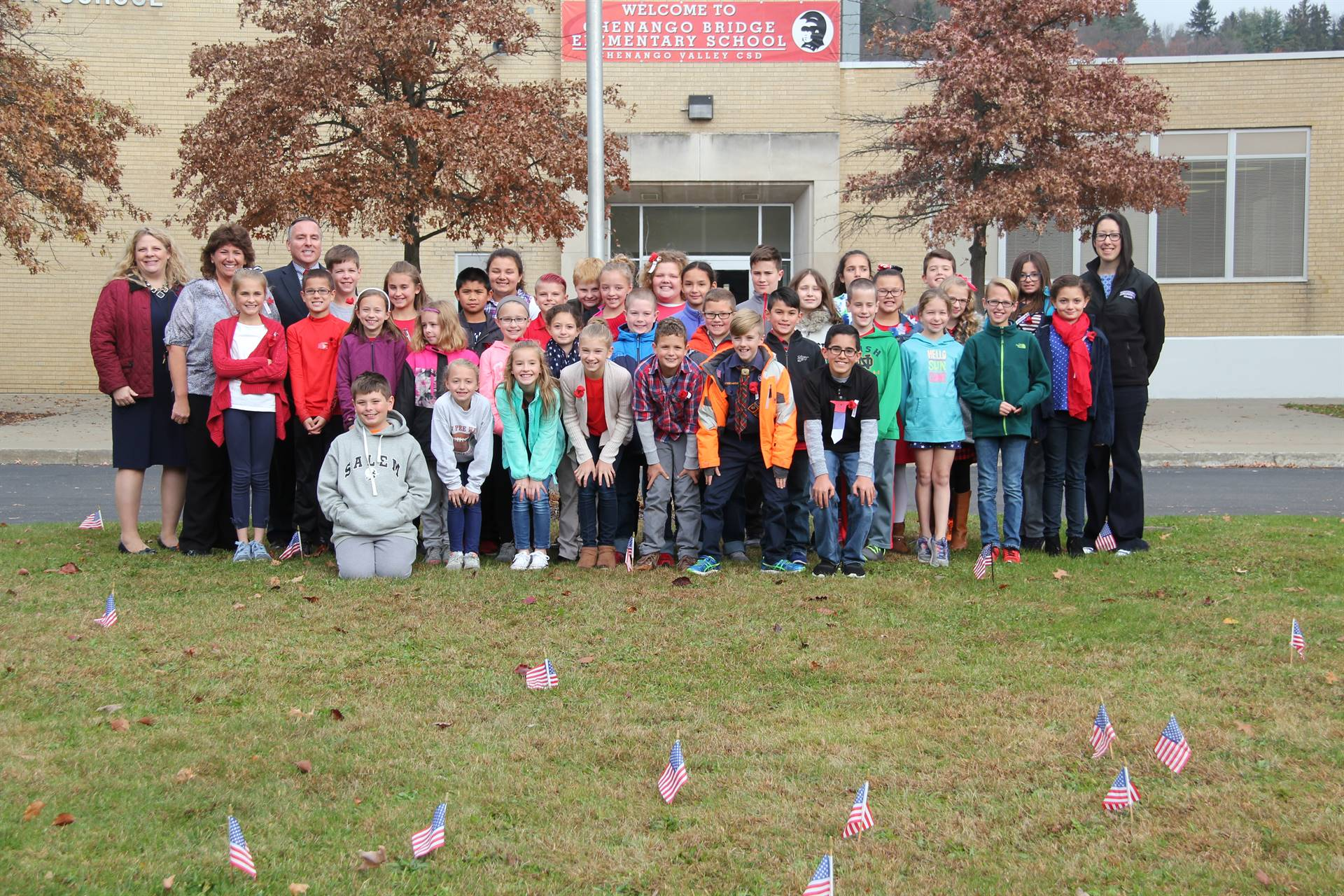 wide shot of student council and c v staff with flags in front of them