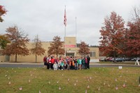 far shot of chenango bridge student council and c v staff with lawn full of flags