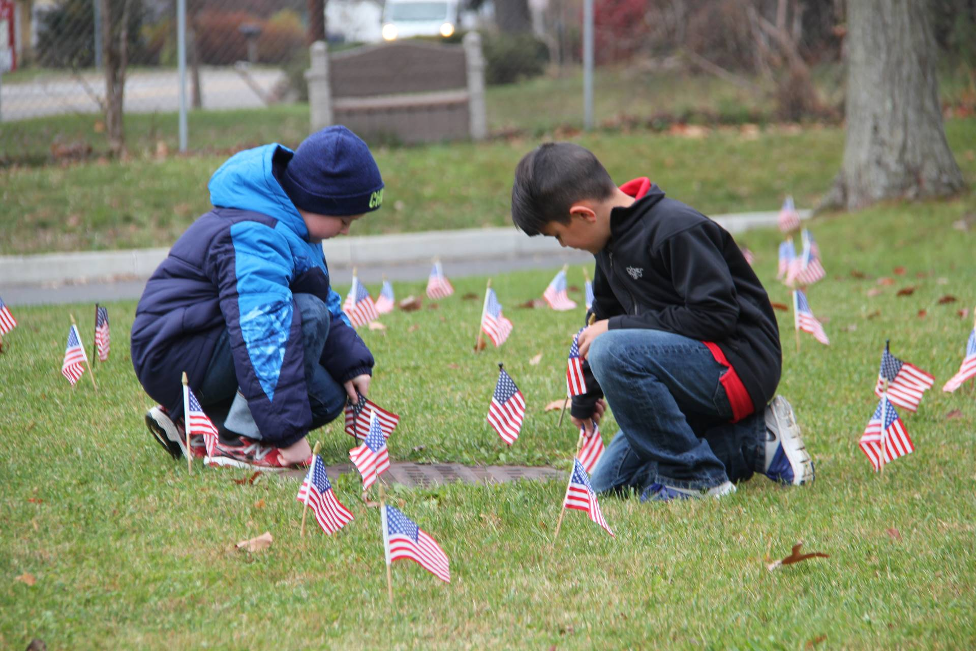 two boys planting american flags in grass