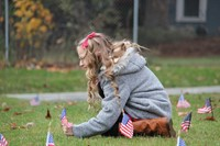 girl planting flag in grass outside chenango bridge elementary