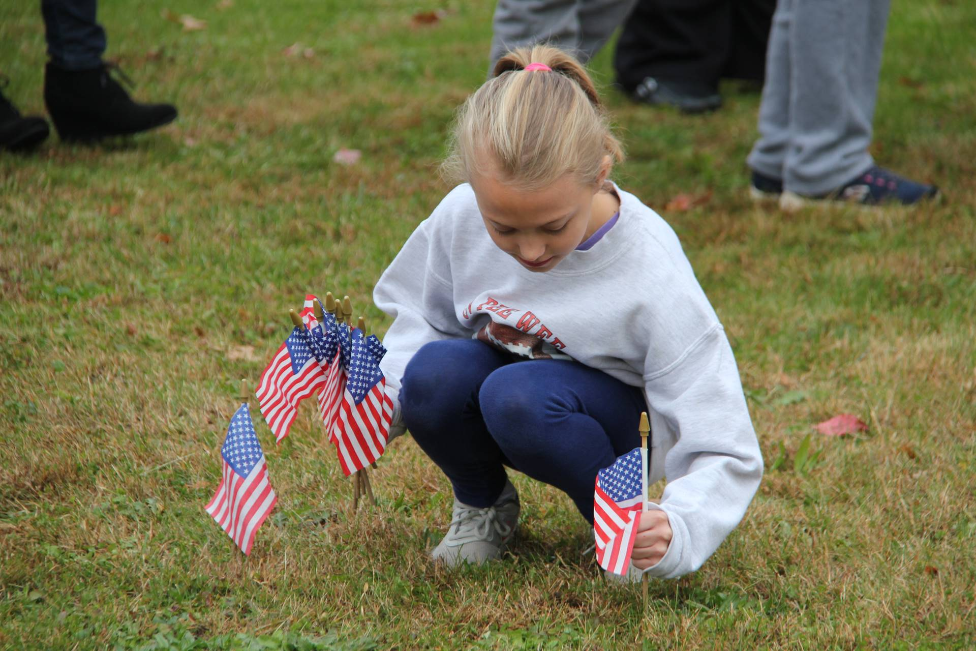 girl plants american flags