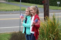 two students smile holding flags