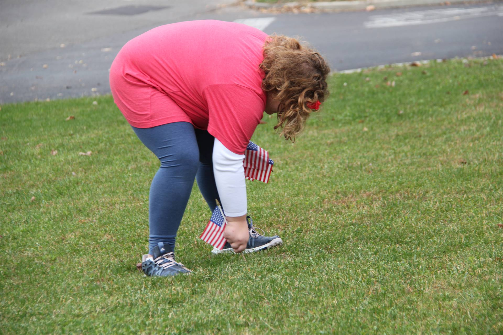 girl plants american flag in grass