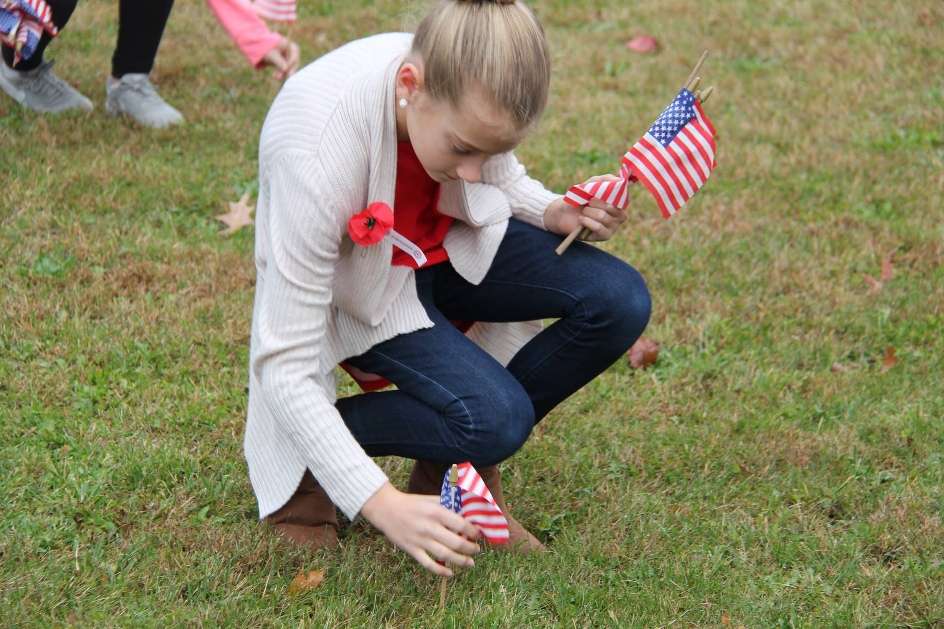 student plants american flag in grass