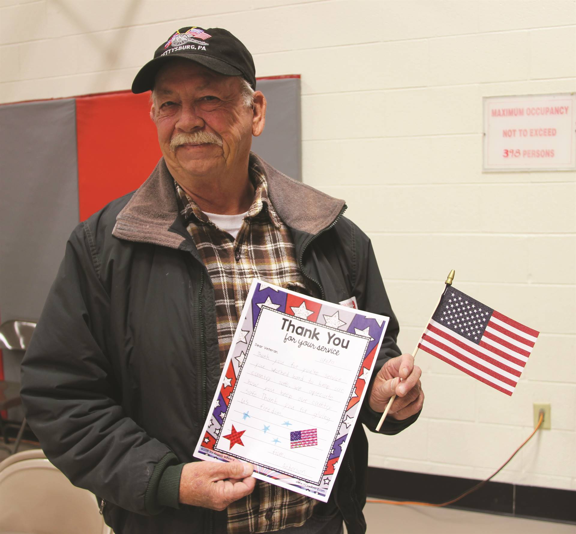 veteran holding up thank you card and flag