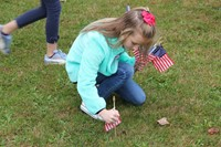 student plants flag in grass