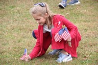 girl planting flag in grass